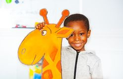 Portrait of black smiling little boy with giraffe. Portrait of happy black smiling little boy with cardboard giraffe in nursery school class royalty free stock photo