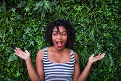A portrait of a black woman standing against green background of bush leaves. A portrait of a black laughing woman standing against green background of bush royalty free stock photography