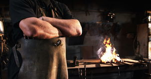 Portrait of blacksmith standing with arms crossed stock footage