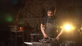 Portrait of a blacksmith in the working atmosphere. A man works with molten metal in the forge. Stock Photo