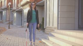 Portrait of a blind girl with a cane walking down the street. Blind girl with a cane walking down the street stock photography