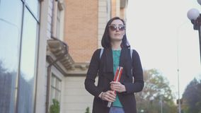 Portrait of a blind girl in glasses with a cane on a city street. Close up stock photography