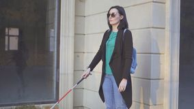 A blind woman wearing glasses with a cane walking in front of shop windows stock photo