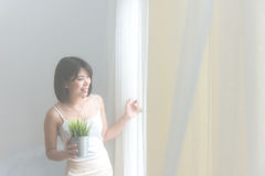 Portrait of blond and attractive woman standing next to the window behind the curtains in the morning, vintage tone,. Soft focus Royalty Free Stock Photo