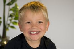 Portrait of blond beautiful 3 or 4 years old caucasian kid smiling happy in joyful face expression  at home looking to ca. Head and shoulders portrait of blond Royalty Free Stock Photos