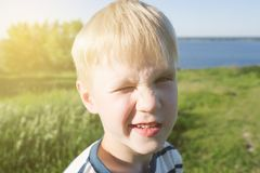 Portrait of blond boy joyful and closing his eye from the sun on nature. stock photo