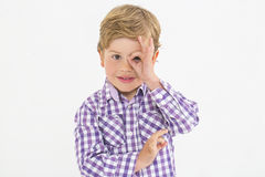 Portrait of blond boy who simulates glasses with his fingers. Blond boy in checked shirt makes a gesture with the hand in the eye simulating some glasses stock photos