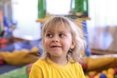 Portrait of a blond boy in a yellow t-shirt. The child smiles and plays in the children`s playroom stock images