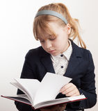 Portrait of blond Caucasian schoolgirl reading textbook Royalty Free Stock Photo