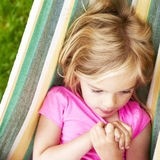 Portrait of blond child girl with blue eyes looking at camera relaxing on a colorful hammock. In a home garden on summer holiday. Vacation lifestyle kid fun Royalty Free Stock Photography