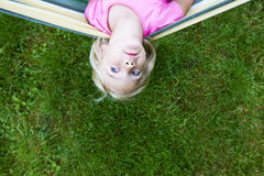 Portrait of blond child girl with blue eyes looking at camera relaxing on a colorful hammock. In a home garden on summer holiday. Vacation lifestyle kid fun Stock Photography