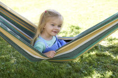 Portrait of blond child girl with blue eyes looking at camera relaxing on a colorful hammock. In a home garden on summer holiday. Vacation lifestyle kid fun Stock Image