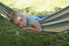 Portrait of blond child girl with blue eyes looking at camera relaxing on a colorful hammock. In a home garden on summer holiday. Vacation lifestyle kid fun Royalty Free Stock Photo