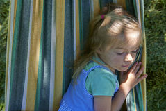 Portrait of blond child girl relaxing on a colorful hammock. In a home garden on summer holiday. Vacation lifestyle kid fun activities Royalty Free Stock Photo