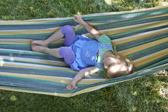 Portrait of blond child girl relaxing on a colorful hammock. In a home garden on summer holiday. Vacation lifestyle kid fun activities Royalty Free Stock Image