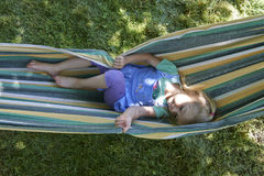 Portrait of blond child girl relaxing on a colorful hammock. In a home garden on summer holiday. Vacation lifestyle kid fun activities Royalty Free Stock Photography