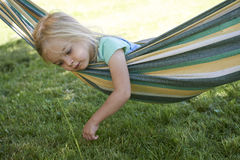 Portrait of blond child girl relaxing on a colorful hammock. In a home garden on summer holiday. Vacation lifestyle kid fun activities Royalty Free Stock Photos