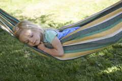 Portrait of blond child girl sleeping, relaxing on a colorful hammock. Portrait of blond child girl relaxing on a colorful hammock in a home garden on summer Stock Photo