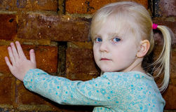 Portrait of blond girl. Portrait of blond 4 year old girl with brick background Royalty Free Stock Photography