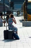 Portrait of blond girl with blue dress and phone waiting with suitcase in front of the train station royalty free stock photo