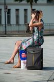 Portrait of blond girl with blue dress and phone waiting with suitcase in front of the train station stock photography