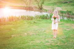 Portrait of a blond girl with a bouquet of flowers on a lake background close-up royalty free stock images