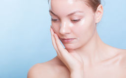 Portrait blond girl in facial mask on blue. Beauty and skin care. Royalty Free Stock Photography