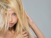 Portrait of blond girl with falling on face hair Stock Photo