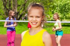 Portrait of blond girl with friends playing behind Royalty Free Stock Image