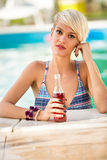 Portrait of blond girl in piscine with refreshing drink Stock Photo