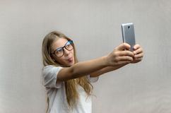 Portrait of a blond girl who takes a selfie on her smartphone. Modern technologies. Young blogger stock photography