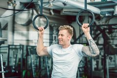 Handsome young man with strong arms hanging on gymnastic rings. Portrait of a blond handsome young man with strong muscular arms smiling while hanging on royalty free stock photography