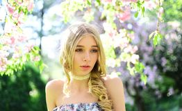 Portrait of blond lady with long curled hair and blue eyes in floral garden. Girl in vintage style outfit enjoying warm stock photography
