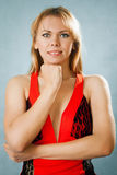 Portrait of a blond lady in red dress. On a blue background Royalty Free Stock Photo