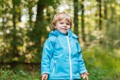Portrait of blond little toddler  boy in blue waterproof raincoa Stock Images