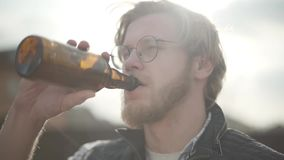 Portrait of the blond man drinking beer outdoors looking away. Bearded man in glasses enjoying his alcohol drink, hair. Portrait of the blond man drinking beer stock footage