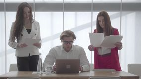 Portrait blond man in glasses sitting in a light comfortable office with netbook. Two girls in formal wear with papers. Standing on either side of the boss stock footage