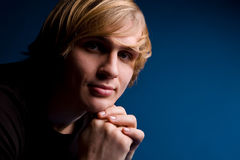 Portrait of blond man over blue background stock photography