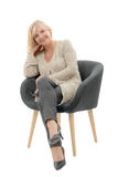 Portrait of blond mature woman relaxing in armchair Royalty Free Stock Photography