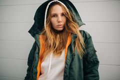 Portrait of blond model in hood and in jacket against gray wall. Background Royalty Free Stock Photos