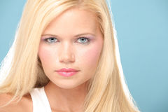Portrait of Blond with Piercing Blue Eyes. Against Blue Background Royalty Free Stock Photography