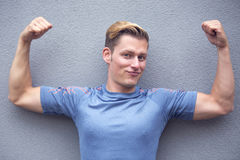 Portrait of blond sportsman showing off his muscles Royalty Free Stock Images