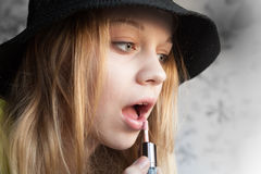 Portrait of blond teenage girl in black hat doing make up Royalty Free Stock Photography