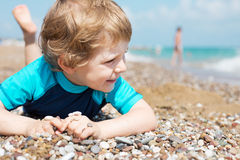 Portrait of blond toddler boy on the beach in summer. Stock Photo