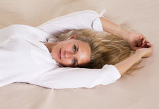 Portrait of a blond woman in bed Stock Photos