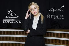 Portrait of a blond woman thinking about money-making. Business concept. Portrait of a blond woman in black suit thinking about money-making. Business concept Stock Image