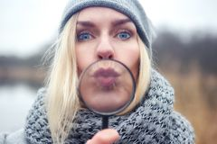 Woman blowing a kiss through a magnifying glass Stock Images
