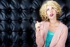 Portrait of blond woman with bubblegum. Portrait of blond curly woman with bubblegum in front of black leather background Royalty Free Stock Photos