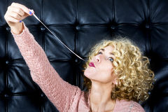 Portrait of blond woman with bubblegum. Portarit of blond curly woman with bubblegum in front of black leather background Royalty Free Stock Photos