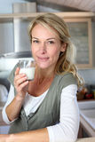 Portrait of blond woman drinking milk Stock Images